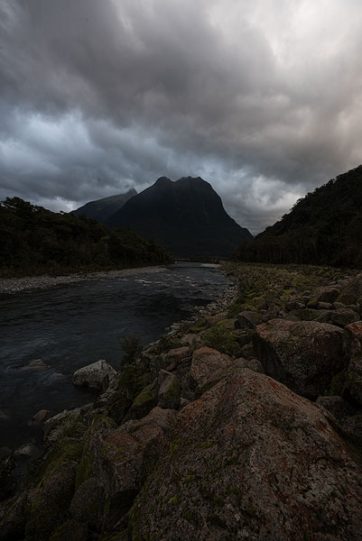 Cloudy mountain landscape with river underexposed